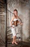 Bella donna di grido dello steampunk con la frusta sulle scala Immagine Stock