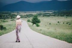 Bella donna di hippy che posa su un campo verde con le montagne sui precedenti Immagine Stock