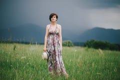 Bella donna di hippy che posa su un campo verde con le montagne sui precedenti Fotografie Stock