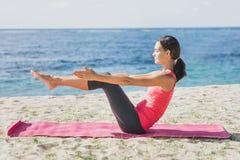 Bella donna di misura che fa allungando esercizio di yoga Immagini Stock
