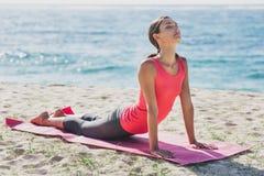 Bella donna di misura che fa allungando esercizio di yoga Fotografia Stock Libera da Diritti
