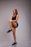 Bella donna di misura nella cima e negli shorts del blac e scarpe da tennis nere che fanno esercizio contro Gray Background Immagine Stock