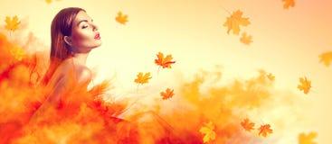 Bella donna di modo in vestito da giallo di autunno con le foglie cadenti immagine stock libera da diritti