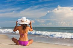 Bella donna di retrovisione alla spiaggia in cappello e bikini Fotografia Stock