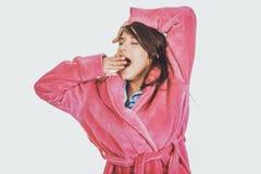 Bella donna di sbadiglio in accappatoio rosa Fotografia Stock Libera da Diritti