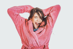 Bella donna di sbadiglio in accappatoio rosa Immagine Stock