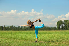 Bella donna di sport che fa allungando esercizio di forma fisica nel parco della città all'erba verde Fotografie Stock Libere da Diritti
