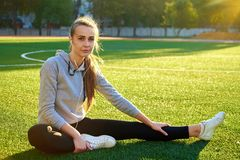 Bella donna di sport che fa allungando esercizio di forma fisica nel parco della città all'erba verde Posizioni di yoga Immagine Stock Libera da Diritti