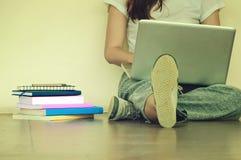 Bella donna di uno studente che si siede con il computer portatile e che si rilassa dentro Fotografie Stock Libere da Diritti