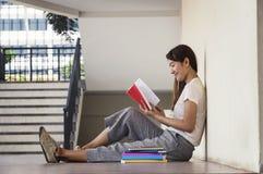 Bella donna di uno studente che si siede con il computer portatile e che si rilassa dentro Immagine Stock