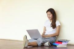 Bella donna di uno studente che si siede con il computer portatile e che si rilassa dentro Fotografia Stock
