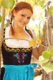 Bella donna in Dirndl fra i fogli di autunno Fotografia Stock Libera da Diritti