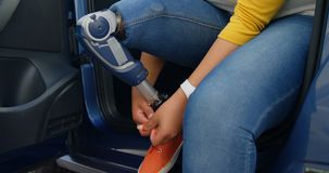 Bella donna disabile che lega laccetto nell'automobile 4k video d archivio