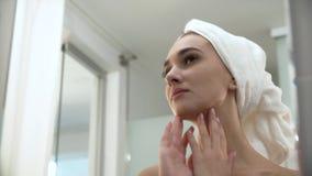 Bella donna dopo la doccia che esamina in specchio il bagno video d archivio