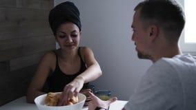 Bella donna dopo la doccia con l'asciugamano scuro sulla sua testa che mangia i croissant e che beve caffè Parlando con suo ragaz archivi video