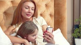 Bella donna e la sua piccola figlia sveglia che per mezzo dello Smart Phone a casa insieme archivi video