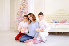 Bella donna e madre preoccupantesi con un exchang di due bambini maschii Fotografia Stock