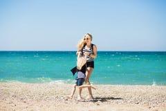 Bella donna e sua la figlia affascinante che riposano sulla spiaggia Immagine Stock