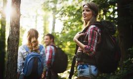 Bella donna ed amici che fanno un'escursione nella foresta Immagine Stock