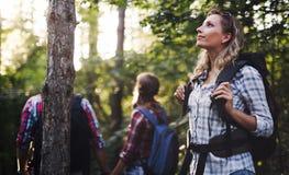 Bella donna ed amici che fanno un'escursione nella foresta Immagini Stock