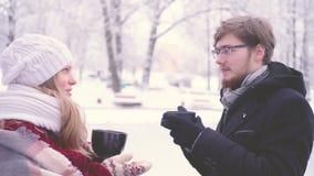 Bella donna ed uomo barbuto con i vetri che parlano e che bevono cacao caldo dalle tazze in loro mani nel parco di inverno stock footage