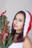 Bella donna egiziana casuale felice sorridente nell'albero di Natale della tenuta del costume del Babbo Natale fotografia stock libera da diritti