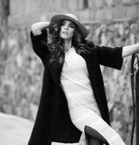 Bella donna elegante nel ove nero d'avanguardia alla moda del cappello e del cappotto Immagine Stock
