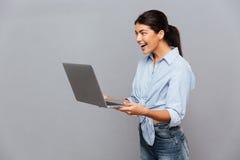 Bella donna emozionante felice che per mezzo del computer portatile Immagini Stock Libere da Diritti