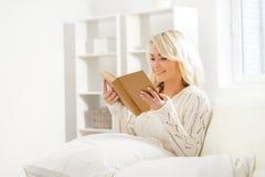 Bella donna emozionante sorridente che legge un libro di mattina Immagini Stock Libere da Diritti