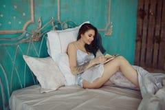 Bella donna emozionante sorridente che legge un libro di mattina Immagini Stock