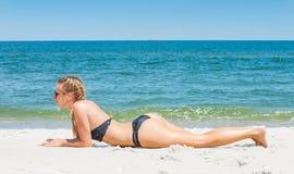 Bella donna esile in bikini che si trova sulla sabbia sulla spiaggia immagine stock libera da diritti