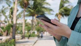Bella donna esile con capelli biondi lunghi in camicia verde che sta la palma vicina e che per mezzo dello smartphone sopra fondo stock footage