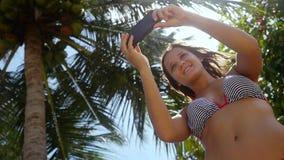 Bella donna esile con capelli castana lunghi che stanno la palma vicina e che fanno selfie sul telefono cellulare su un cielo blu archivi video