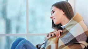 Bella donna felice avvolgersi su in plaid caldo che si siede sulla finestra al fine settimana di inverno stock footage
