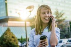 Bella donna felice che cammina e che scrive o che legge il messaggio degli sms sulla linea su uno Smart Phone Immagini Stock