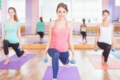 Bella donna felice che fa esercizio di forma fisica con peso in mani Fotografia Stock