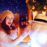 Bella donna felice che fa pupazzo di neve sotto la neve magica di inverno immagine stock libera da diritti