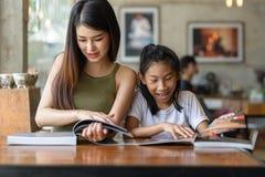 Bella donna felice che legge un libro con sua sorella, stile di vita Immagini Stock