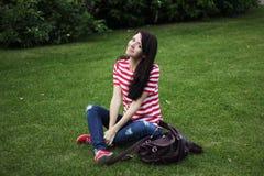Bella donna felice che si siede sull'estate verde del campo Fotografia Stock