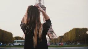 Bella donna felice che sta vicino alla torre Eiffel a Parigi, Francia Ragazza che sorride e che invia il bacio del colpo alla mac video d archivio