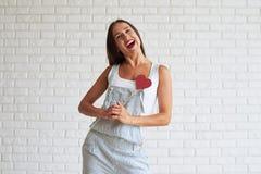 Bella donna felice che tiene vicino del suo cuore di carta rosso del cuore Fotografia Stock