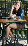 Bella donna felice con il telefono mobile in caffè fotografia stock