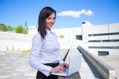 Bella donna felice di affari che per mezzo del computer portatile sulla via Fotografia Stock Libera da Diritti