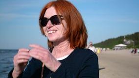 Bella donna felice di affari che ride e che guarda intorno sulla spiaggia archivi video