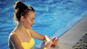 Bella donna felice nella piscina con lo smartphone in sua mano archivi video