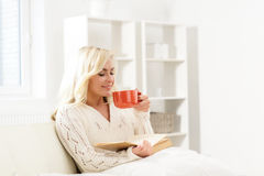Bella donna felice sorridente che legge un libro e che ha una tazza di Fotografie Stock Libere da Diritti