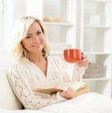 Bella donna felice sorridente che legge un libro e che ha una tazza di caffè di mattina Fotografia Stock Libera da Diritti