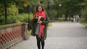 Bella donna felice splendida che cammina nel parco di autunno, ragazza dello studente che parla sul telefono e che sorride sulla  video d archivio