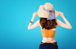 Bella donna graziosa che indossa un cappello di paglia e un vestito sexy su fondo blu con il concetto di estate immagine stock