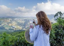Bella donna graziosa che prende le foto delle piantagioni di tè facendo uso del suo telefono cellulare immagine stock
